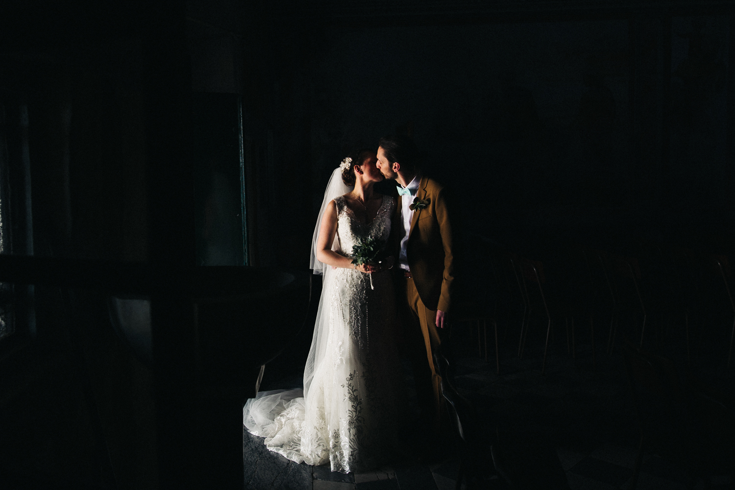 a bride and groom stand in the darkness, only them as illuminated by the light