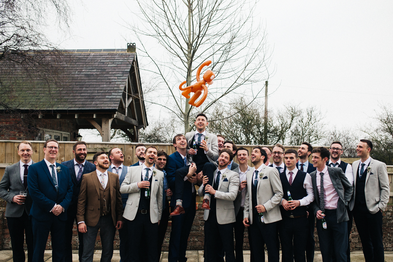 a large group of men at a wedding hold the groom on their shoulders, and inflatable monkey is in the air above them