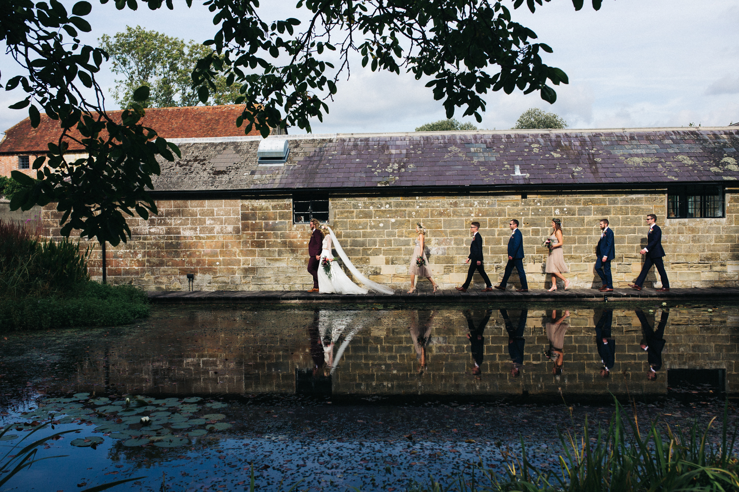 a bride, groom and their bridal party walk along a pond, their reflection shows in the water