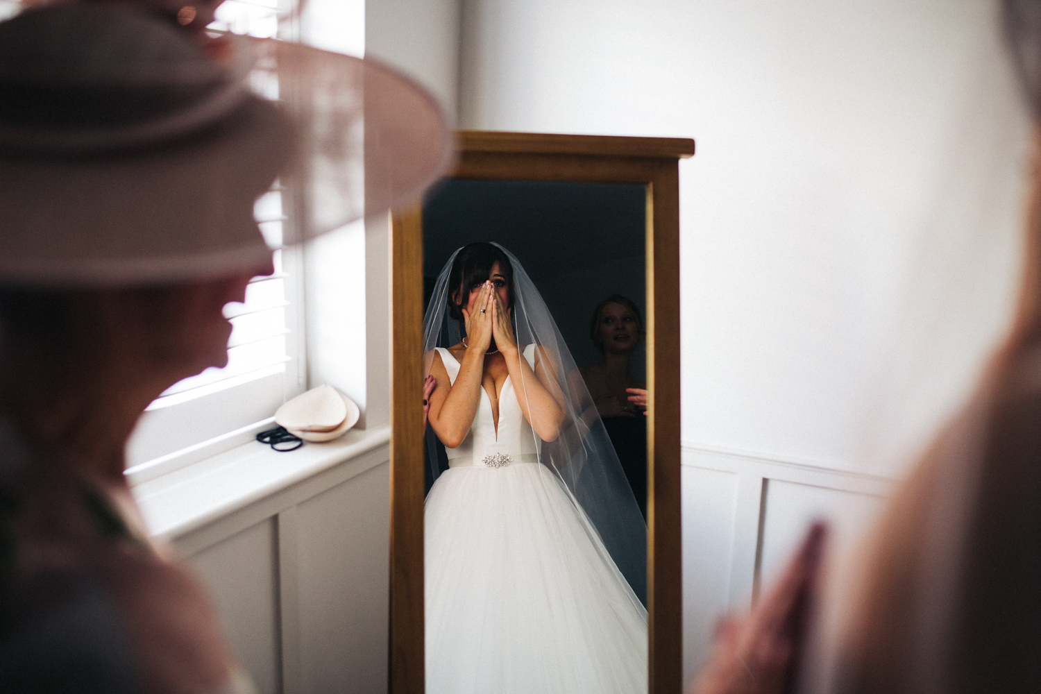 a bride looks awed at her own reflection in her wedding dress