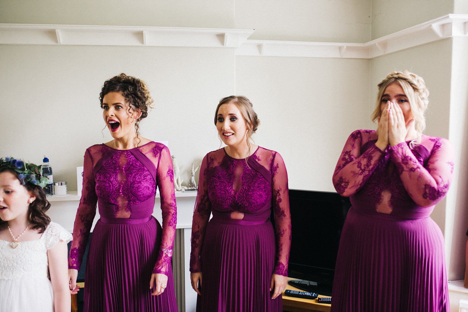 bridesmaids look amazed when seeing the bride in her dress for the first time