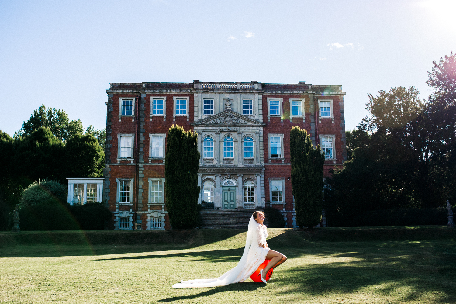 a bride hops across the lawn on an orange spacehopper in front of a county house