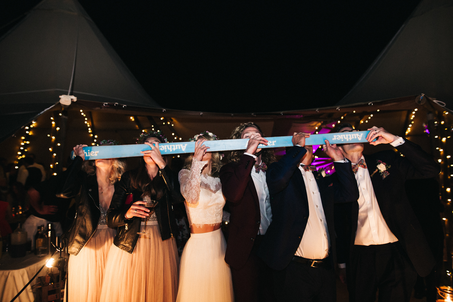 guests at a wedding use a shot-ski to do a line of shots at a wedding evening reception