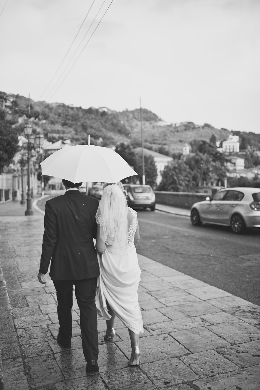 black and white photo of a bride and groom walking down the street with an umbrella in the rain. destination wedding photography in italy, rome. stop motion wedding films