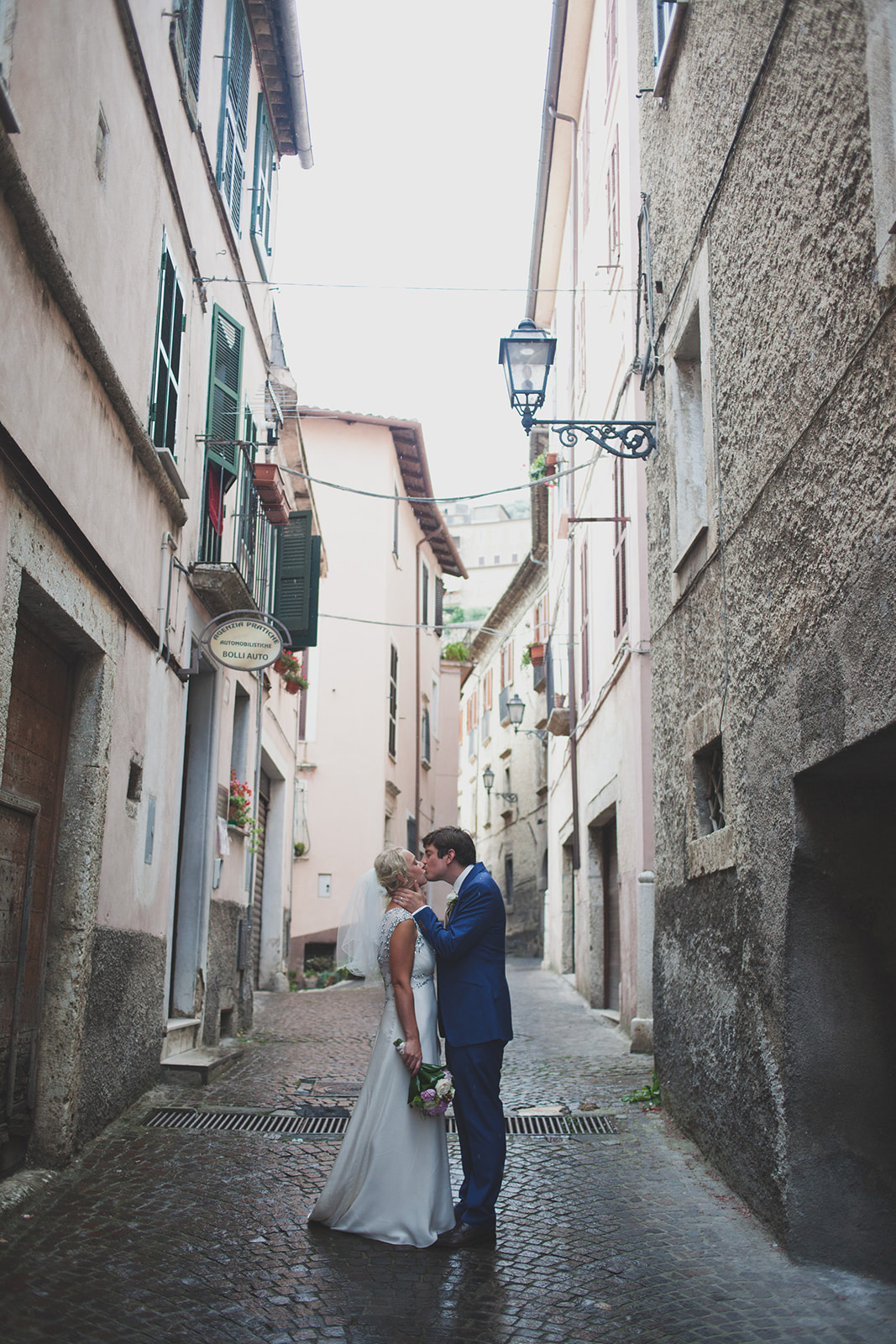 a bride and groom stand in a tall italian street kissing. destination wedding photography in italy, rome. stop motion wedding films