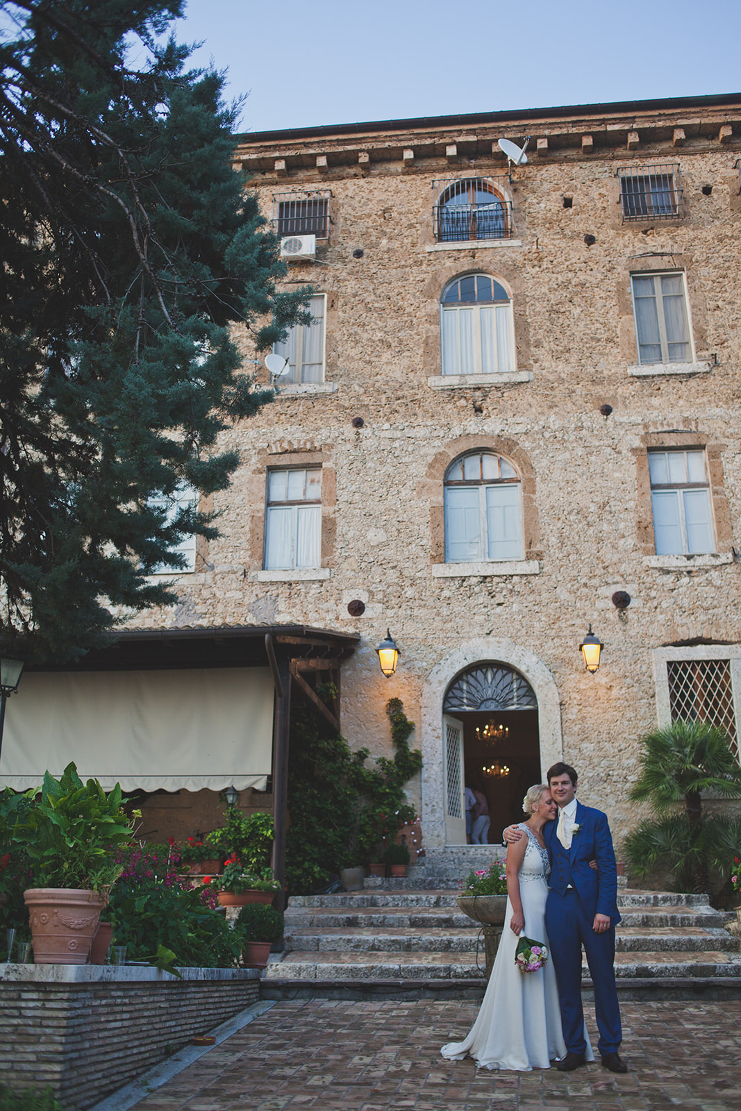 a bride and groom stand outside a typically italian tall hotel. destination wedding photography in italy, rome. stop motion wedding films