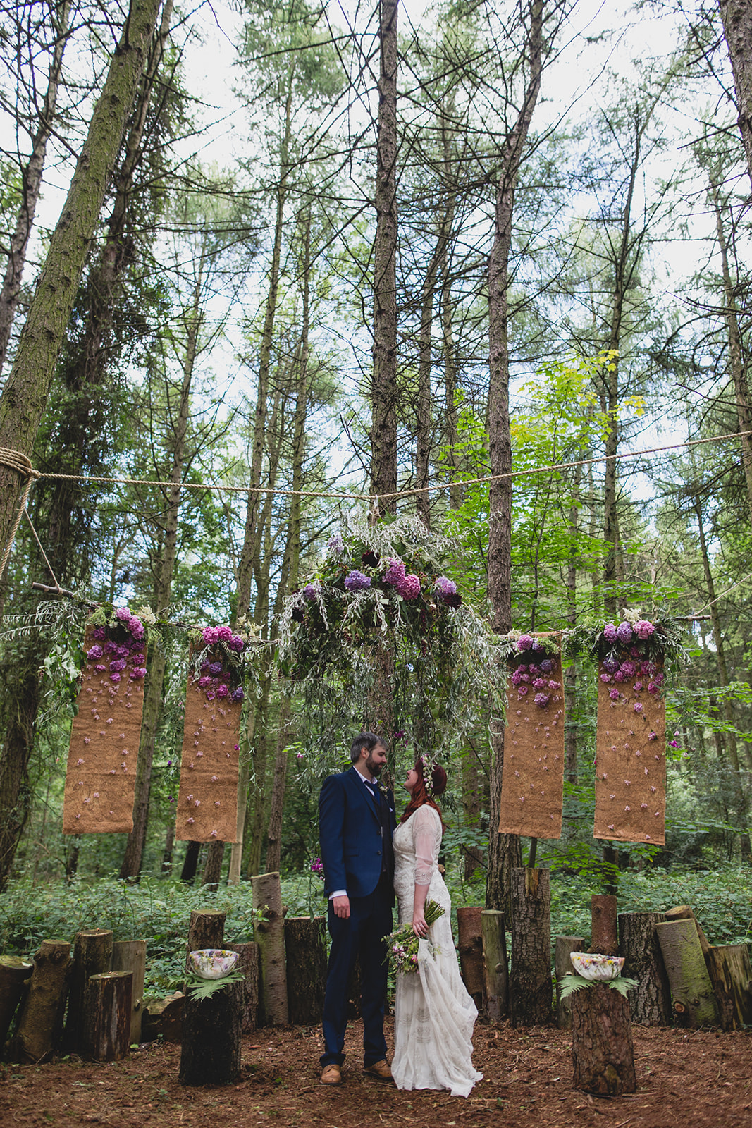 a bride and groom stand under a rustic and flowery alter in the woods. camp katur wedding north yorkshire tipi wedding venue glamping. stop motion wedding films uk