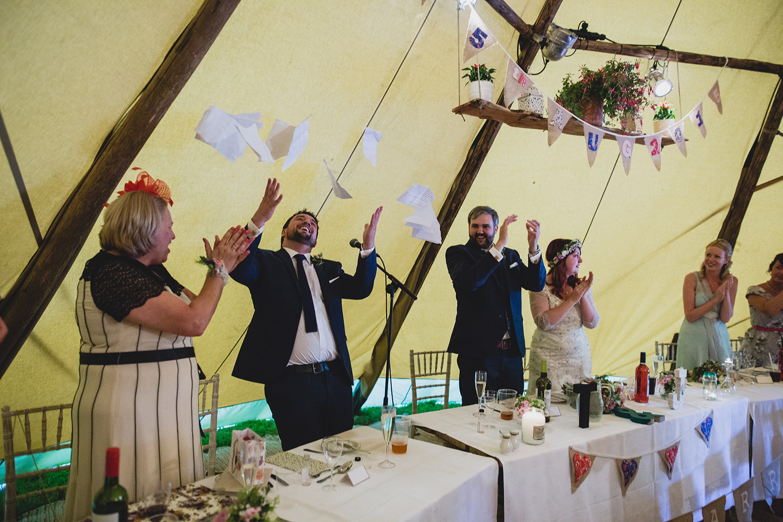 a best man throws his notes in the air following his speech. camp katur wedding north yorkshire tipi wedding venue glamping. stop motion wedding films uk