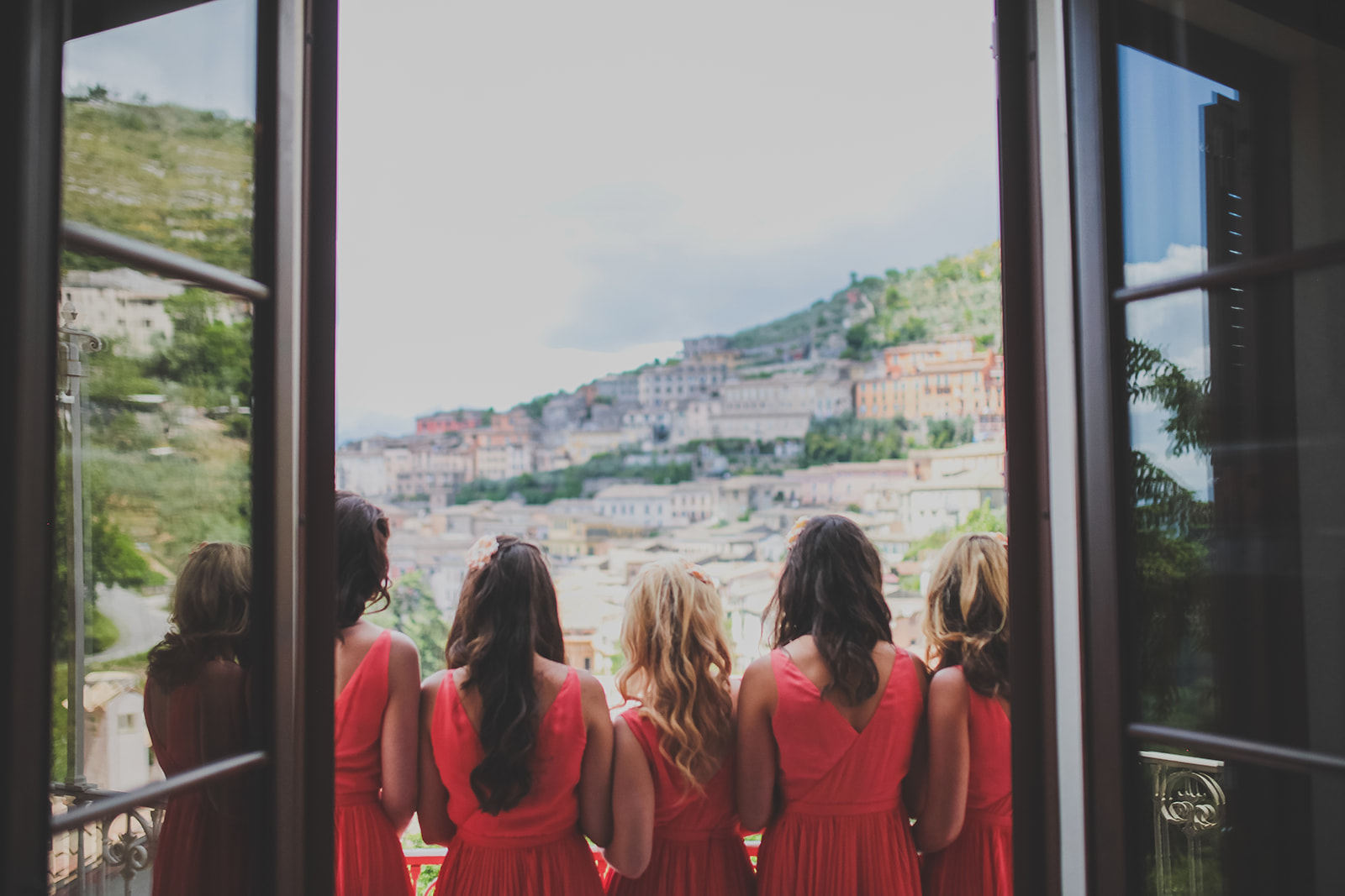 bridesmaids stand and look out of a balcony window out to views of the italian hills. destination creative wedding photography italy. stop motion wedding films uk