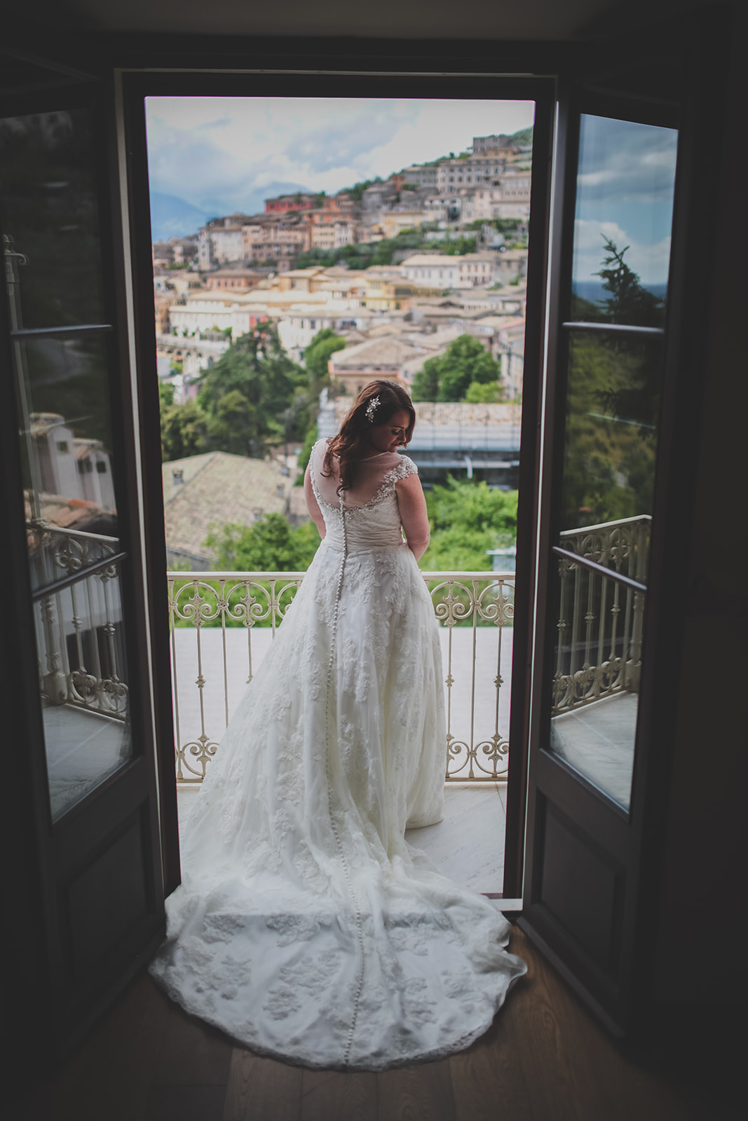 a bride stands with her back to the camera with views of the italian hills in the background. destination creative wedding photography italy. stop motion wedding films uk