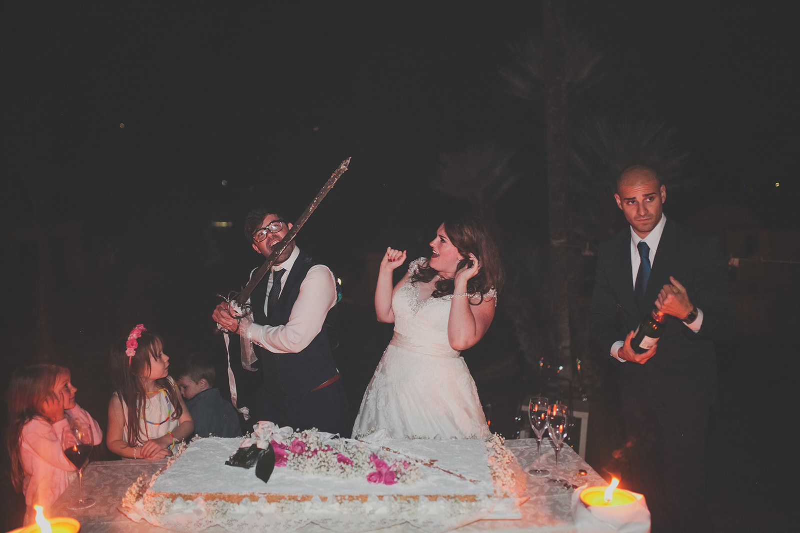 a bride and groom cut their wedding cake with a sword. destination creative wedding photography italy. stop motion wedding films uk