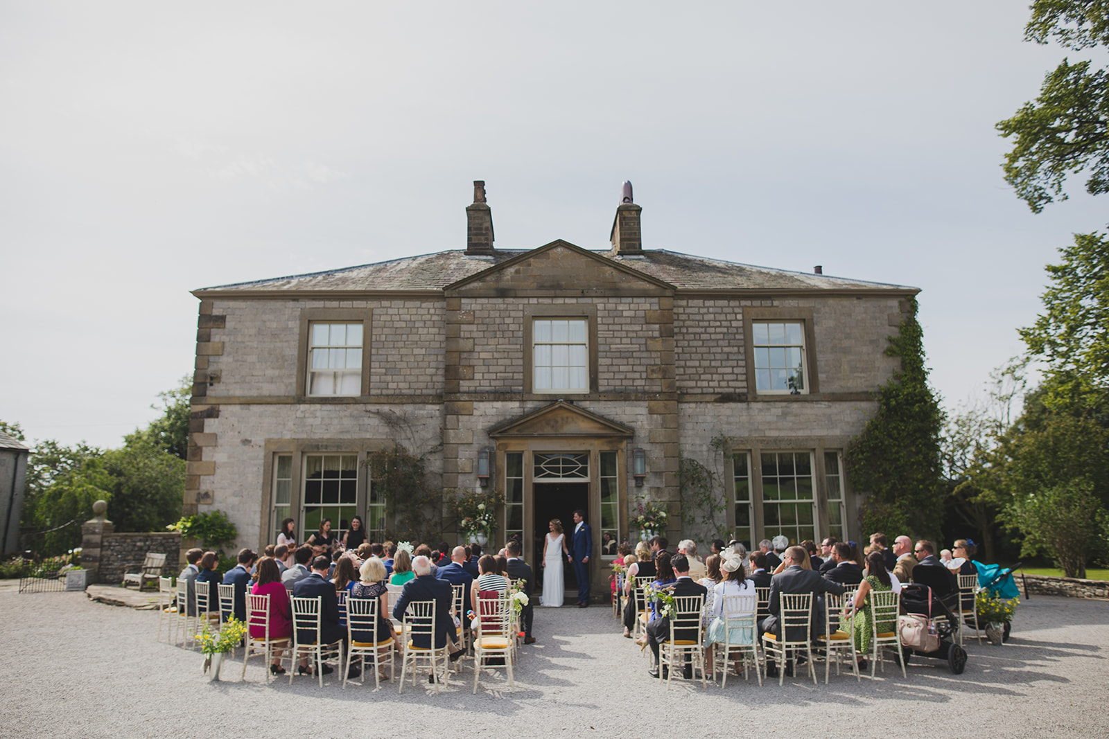 a wide shot of a bride and groom's ceremony in front of a grand country house. underlay grange marquee wedding lake district. stop motion wedding films uk