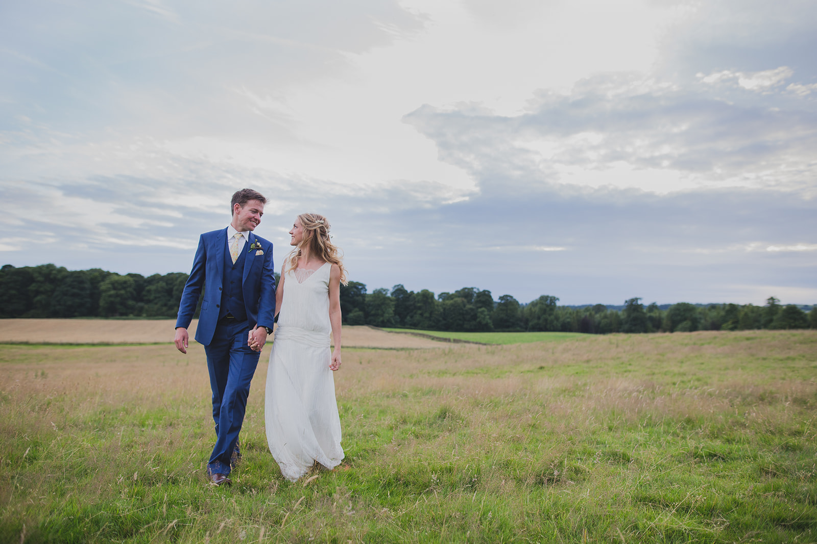 a bride and groom smile at each other walking through a field. underlay grange marquee wedding lake district. stop motion wedding films uk