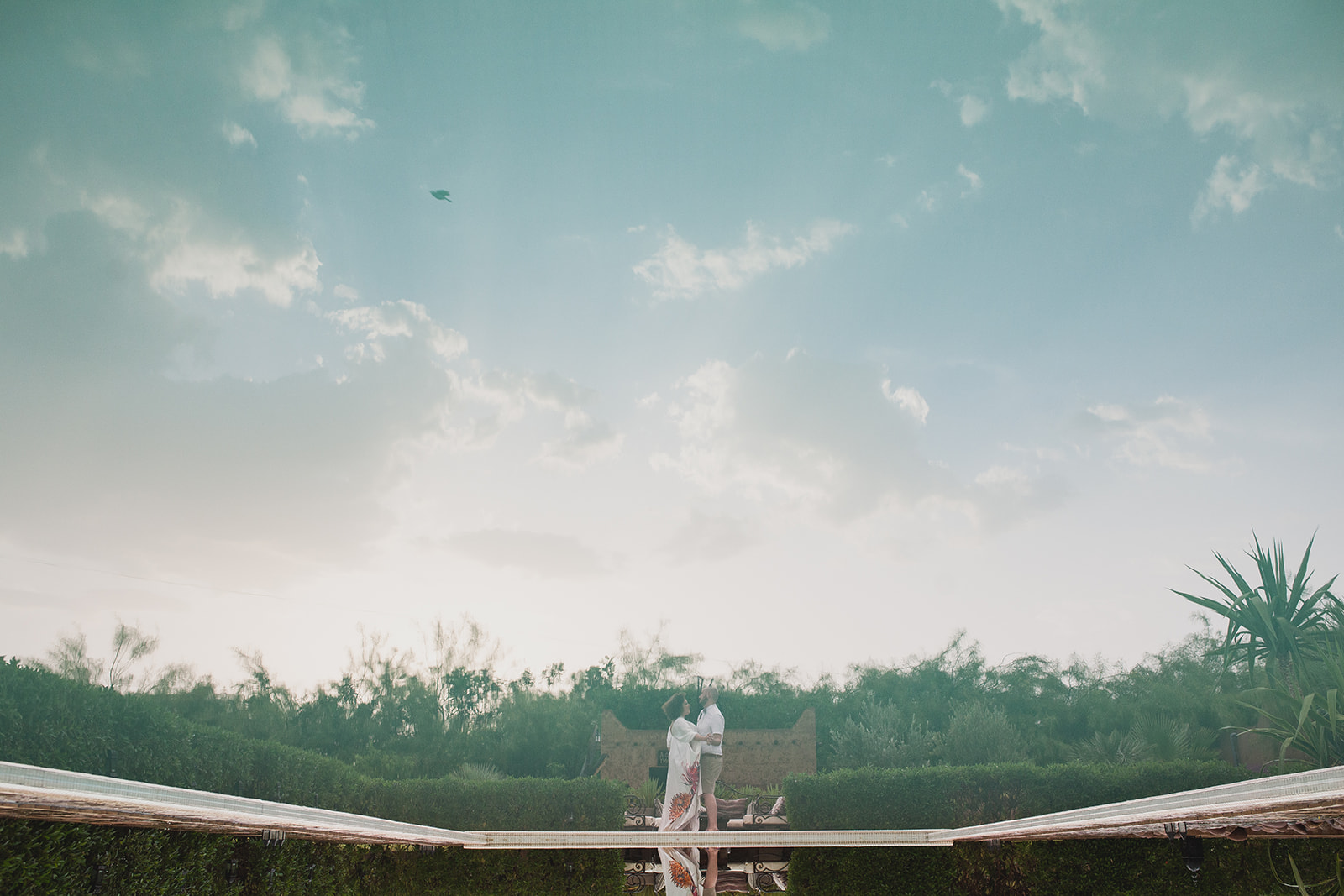 a bride and groom's reflection in the pool. fawakay villas marrakech wedding morrocco wedding photography. stop motion wedding films uk