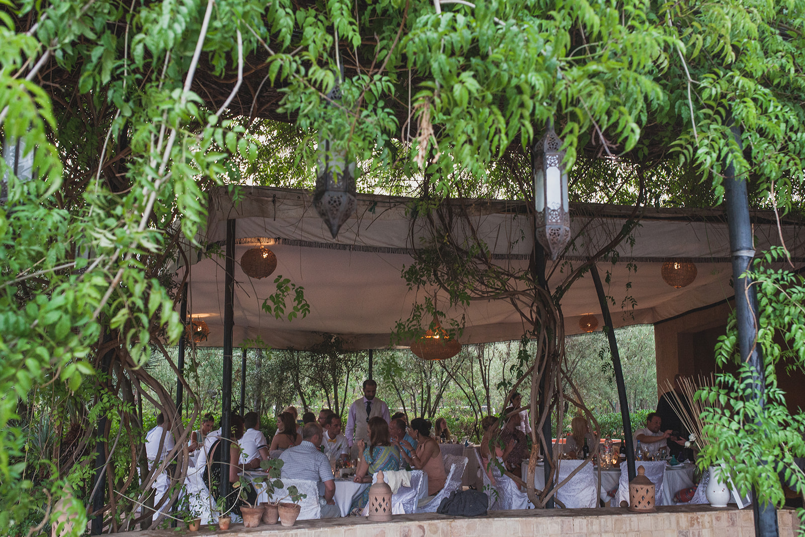 a wide shot of the guests sitting in a botanical looking marquee. fawakay villas marrakech wedding morrocco wedding photography. stop motion wedding films uk