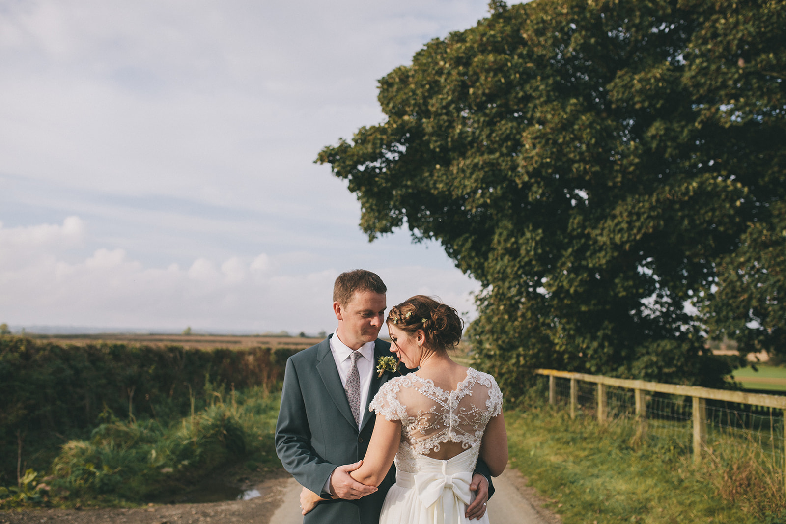 a bride and groom stand close, fields in the background. star inn at harome near helmsley, north yorkshire wedding photographer. stop motion wedding films uk.