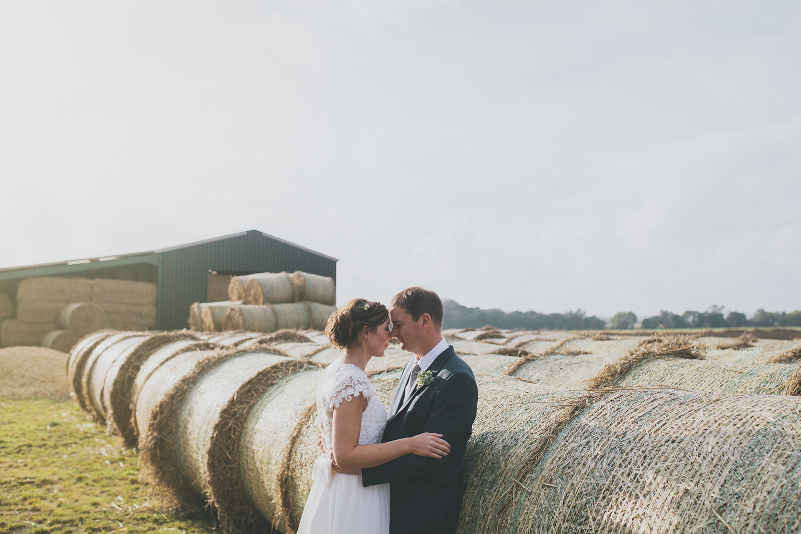 bride and groom are close, standing in front of a barn and haybales. star inn at harome near helmsley, north yorkshire wedding photographer. stop motion wedding films uk.