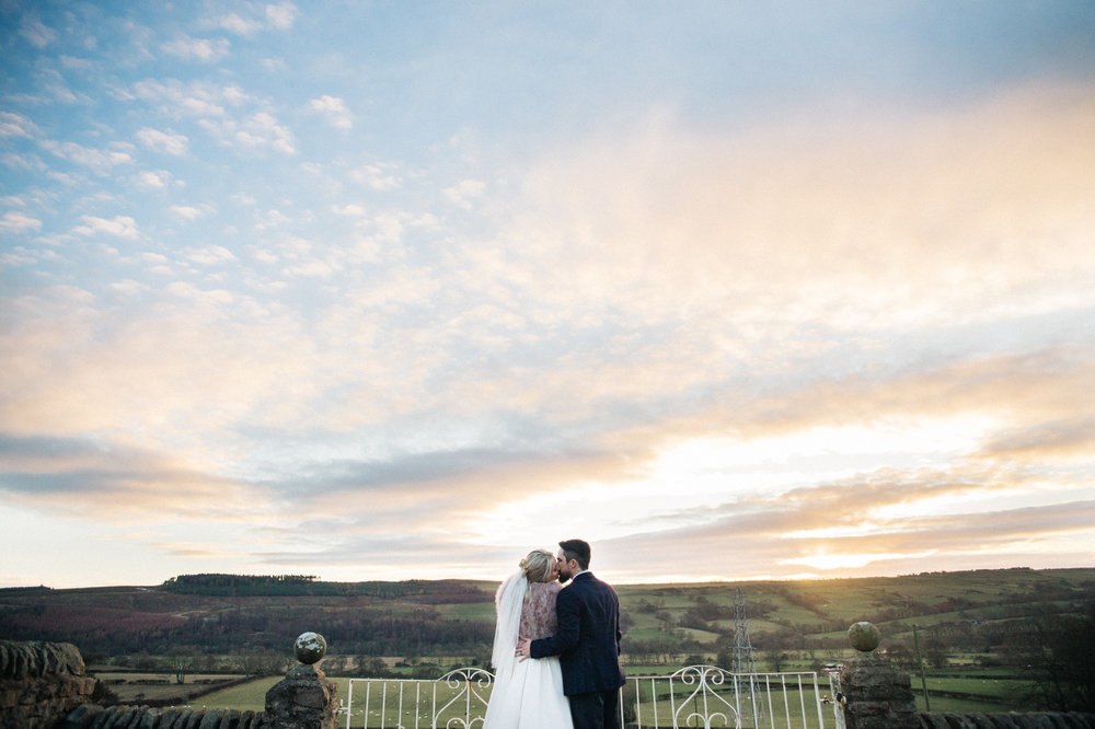 a couple stand kissing, wide shot with a view of the hills and sunset behind them. intimate winter wedding north east wedding photographer, stop motion wedding films uk