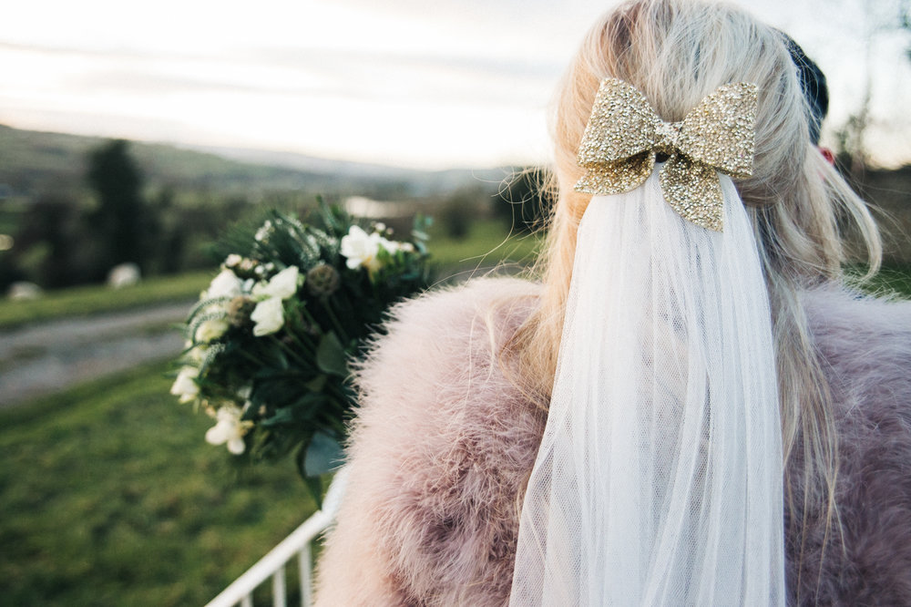 a shot of the bride from behind, she wears a fur coat and a gold glittery bow in her hair. intimate winter wedding north east wedding photographer, stop motion wedding films uk