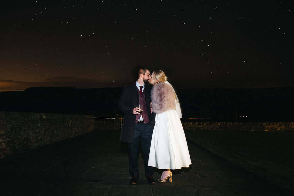 a nighttime shot of the bride and groom against a starry clear sky. intimate winter wedding north east wedding photographer, stop motion wedding films uk