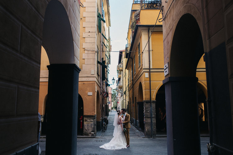 a bride and groom stand in a typically italian street. destination wedding hotel monte rosa chiavari italy. stop motion wedding films uk