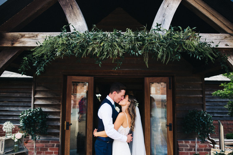 a bride and groom kiss under a barn doorway. sandhole oak barn wedding congleton cheshire. stop motion wedding films uk