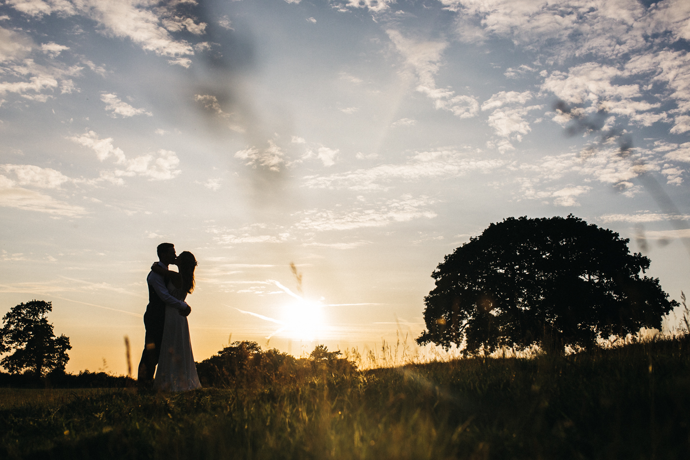 a bride and groom silhouetted against the sunset in a field. sandhole oak barn wedding congleton cheshire. stop motion wedding films uk
