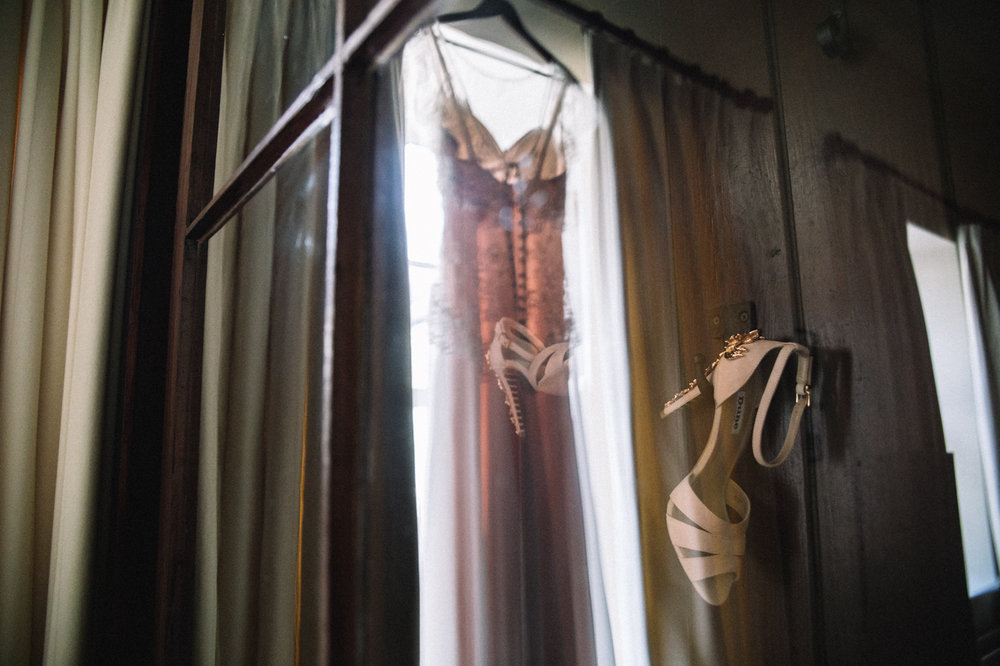 a blush pink dress and shoes hanging in a wardrobe. eshott hall wedding newcastle northumberland wedding photography. stop motion wedding films uk