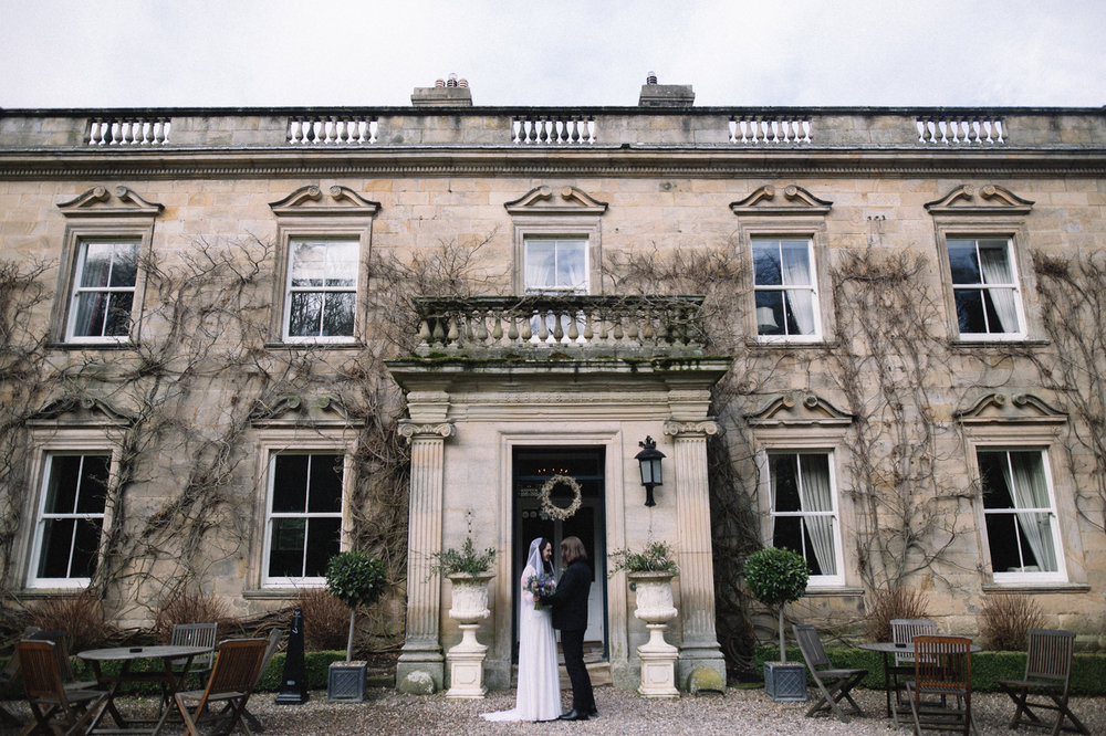 a bride and groom stand together in front of a country house. eshott hall wedding newcastle northumberland wedding photography. stop motion wedding films uk