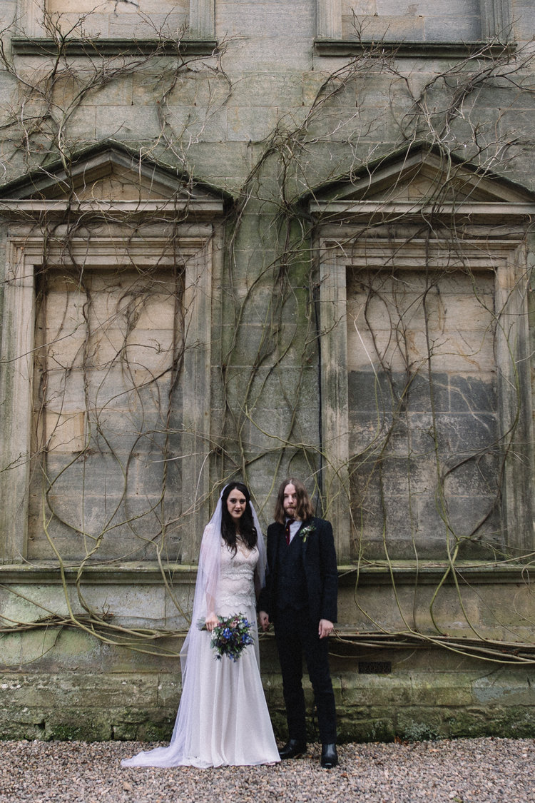 a bride and groom stand facing the camera against an ornate outdoor wall. eshott hall wedding newcastle northumberland wedding photography. stop motion wedding films uk