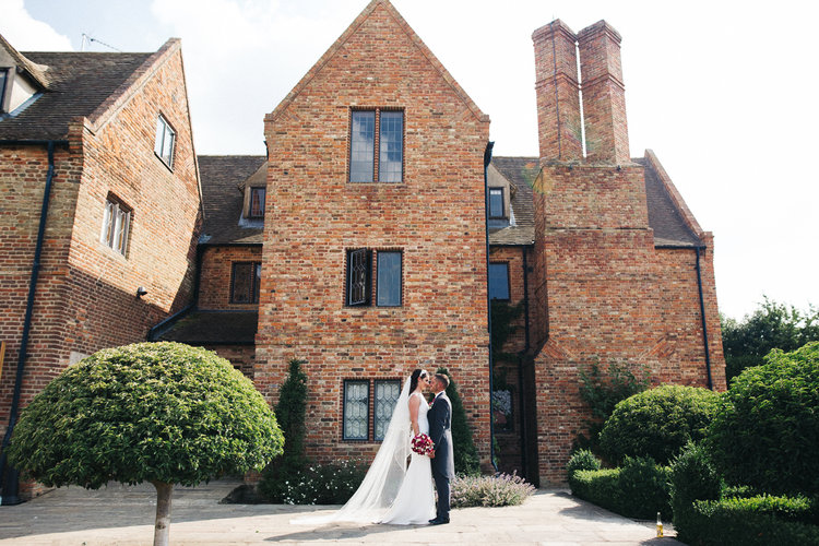 a wide shot of the bride and groom standing in front of their venue. the old hall at ely wedding, cambridge. stop motion wedding films uk
