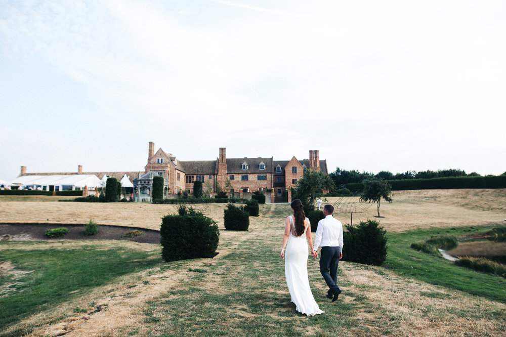 a wide shot of the bride and groom walking towards their venue. the old hall at ely wedding, cambridge. stop motion wedding films uk