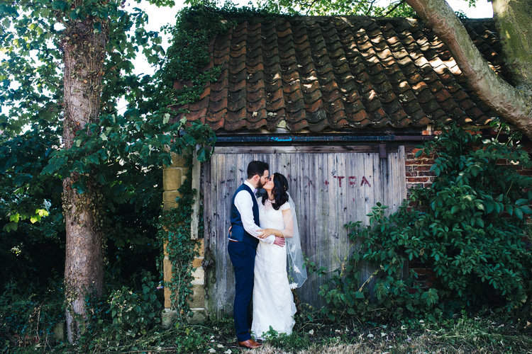 a bride and groom stand in front of a barn door. diy village hall wedding venues north yorkshire northallerton. stop motion wedding films uk