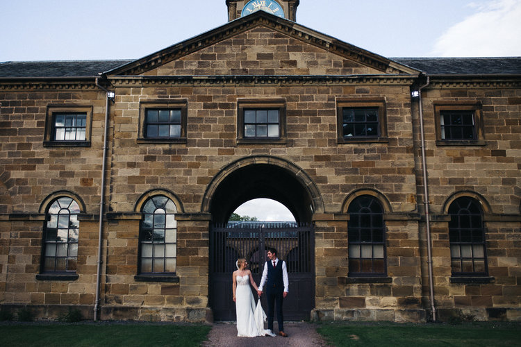 a couple stand in front of a stable building. ormesby hall wedding middlesbrough teesside wedding photography and stop motion wedding films uk
