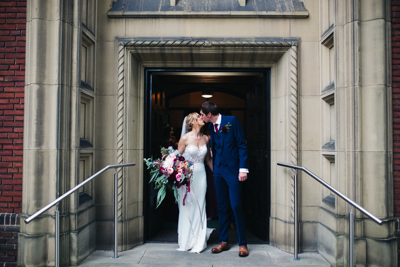 a couple stand in front of church and kiss. ormesby hall wedding middlesbrough teesside wedding photography and stop motion wedding films uk