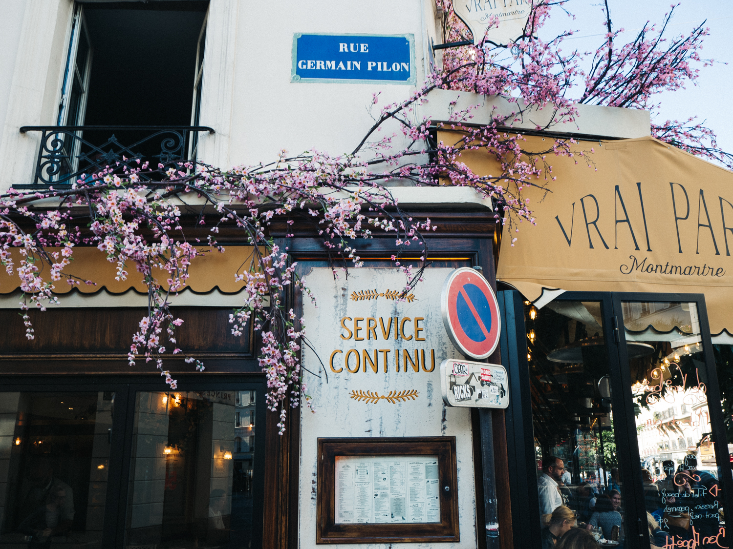 a shot of a blossom-covered shop front in paris. creative travel photography travel blog paris france destination wedding photographer stop motion wedding films uk