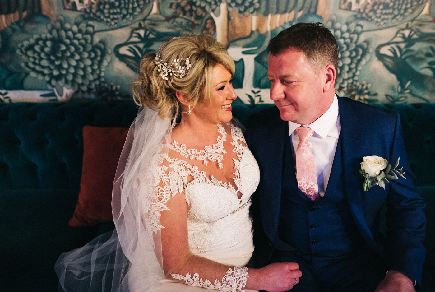 the bride and groom look to each other, they are sitting closely on a sofa. cleveland tontine wedding teesside north yorkshire - relaxed and creative wedding photographer