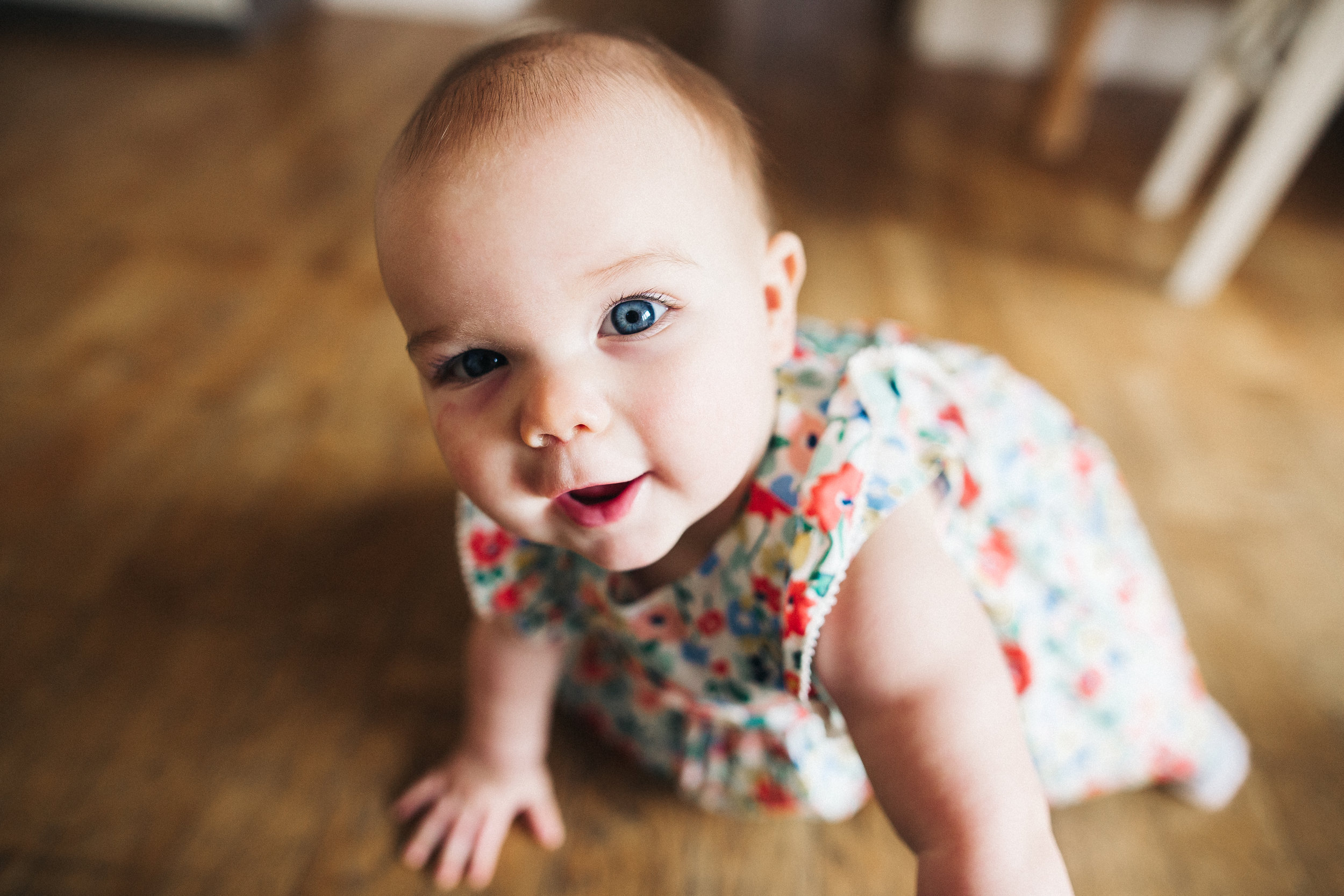 a baby girl crawls in a floral dress. creative relaxed family photography teesside middlesbrough stockton north east
