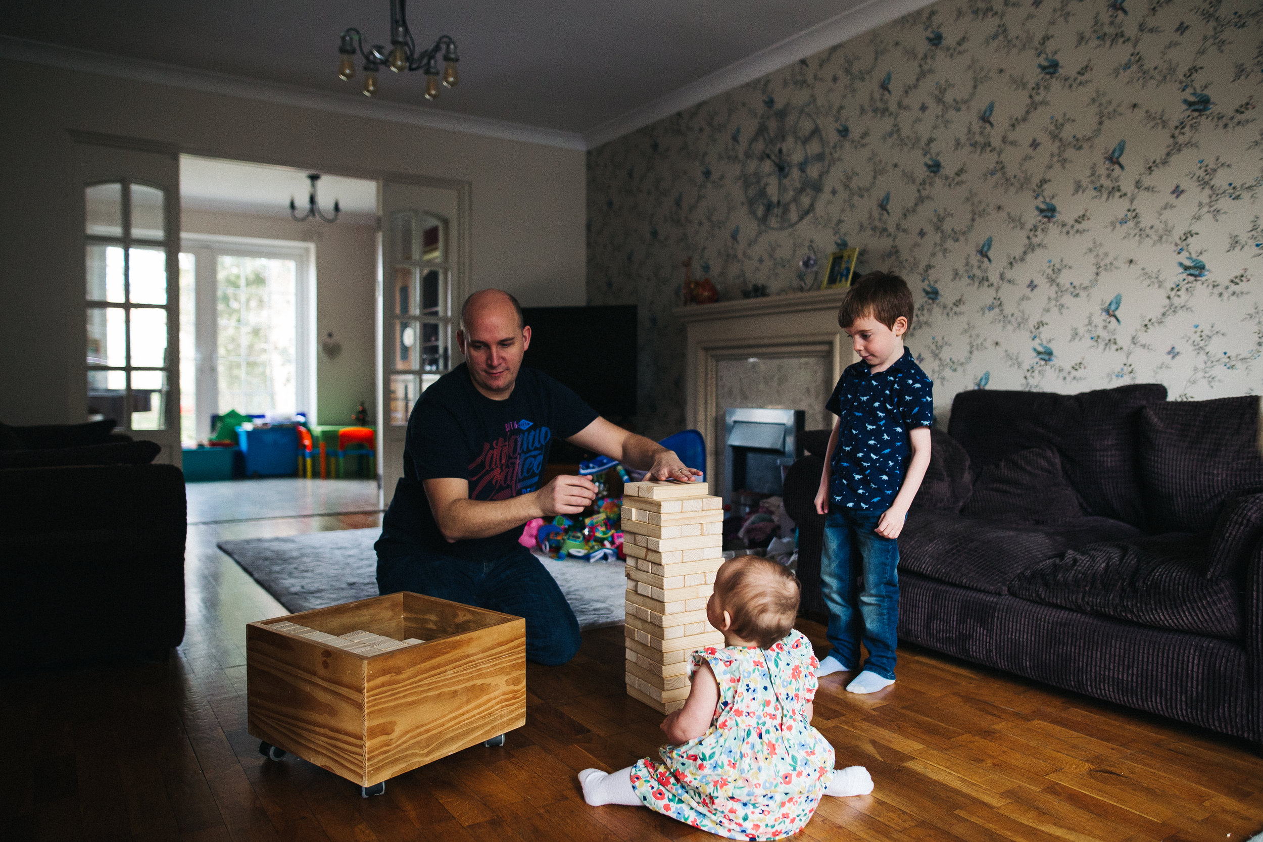 a dad, his son and baby girl are in the living room and building a wooden game. creative relaxed family photography teesside middlesbrough stockton north east