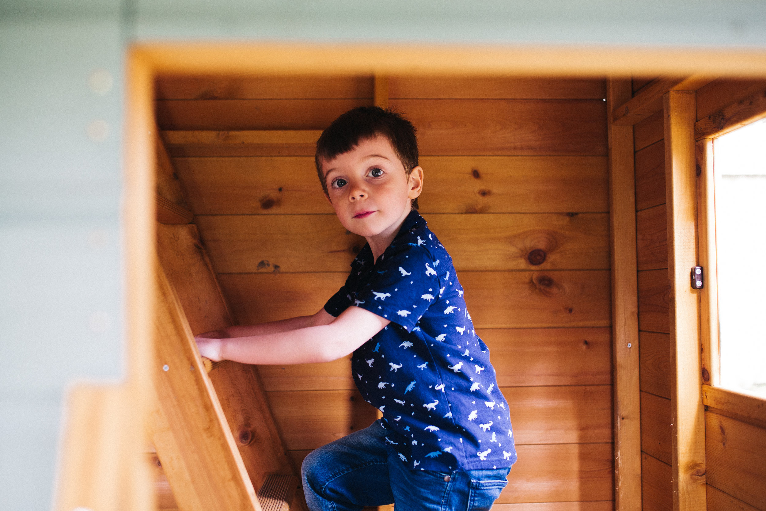 a boy climbs inside his play house. creative relaxed family photography teesside middlesbrough stockton north east