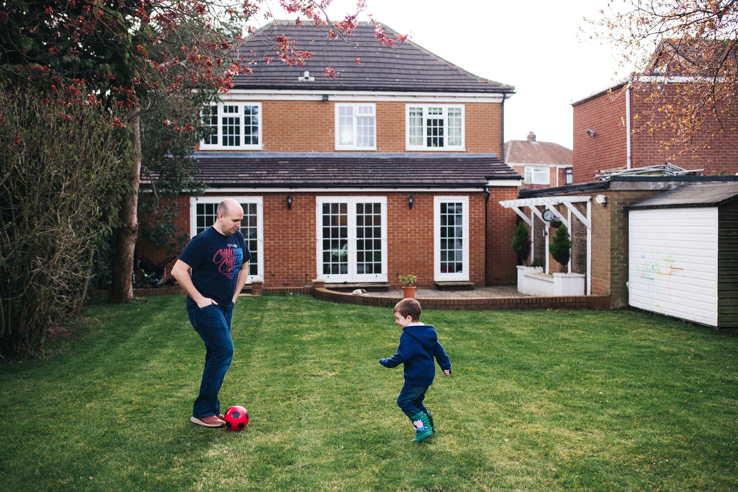 a dad and son play football in their back garden. creative relaxed family photography teesside middlesbrough stockton north east