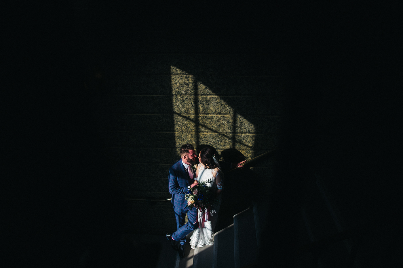 a bride and groom stand in a patch of light on a stairwell. ceremony at st georges hall liverpool, oh me oh my wedding reception, north west wedding photographer