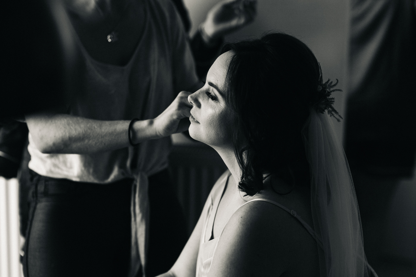 black and white shot of the bride having her make up applied. ceremony at st georges hall liverpool, oh me oh my wedding reception, north west wedding photographer