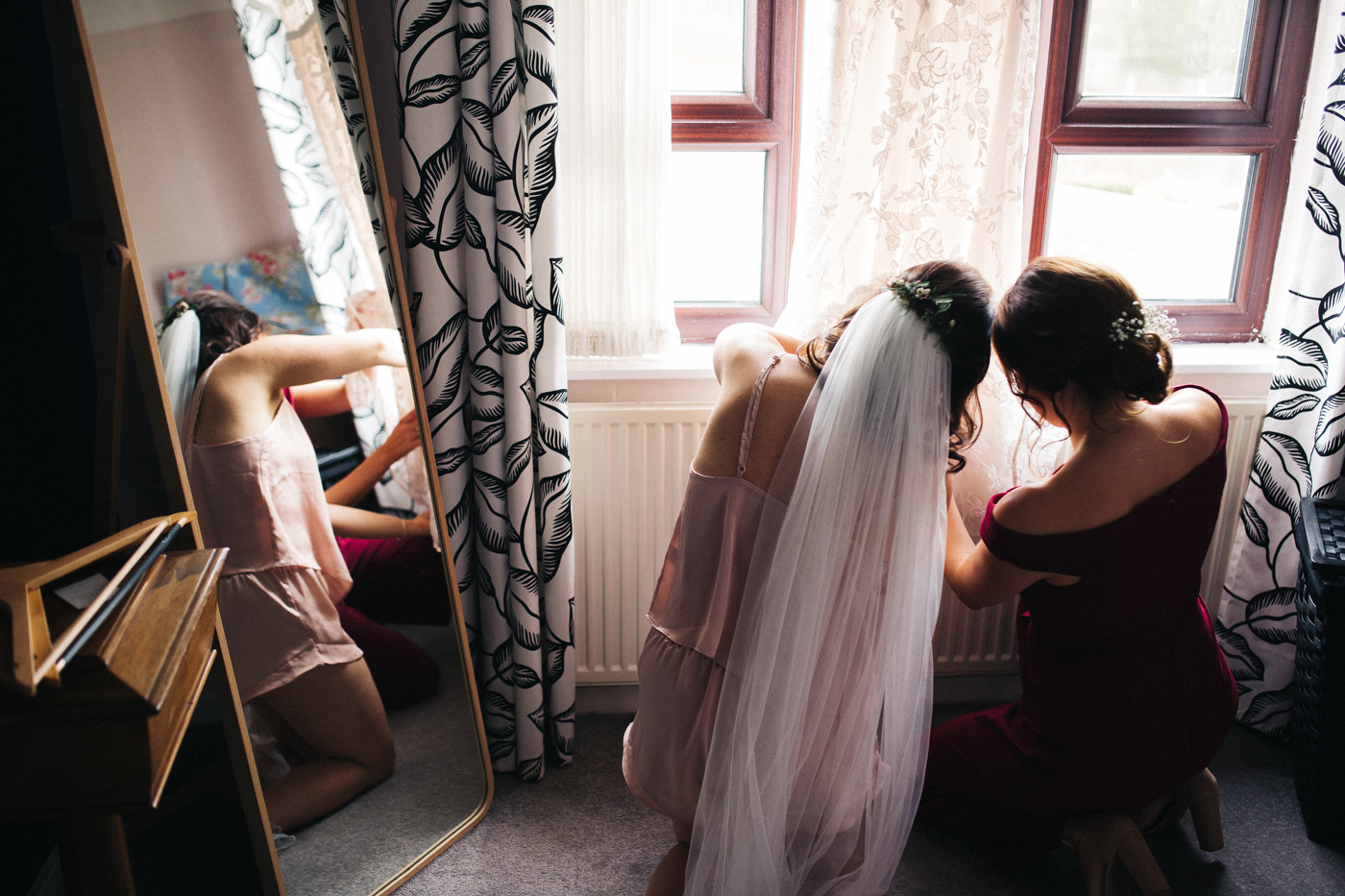 bride and bridesmaid fix the wedding dress before putting it on. ceremony at st georges hall liverpool, oh me oh my wedding reception, north west wedding photographer