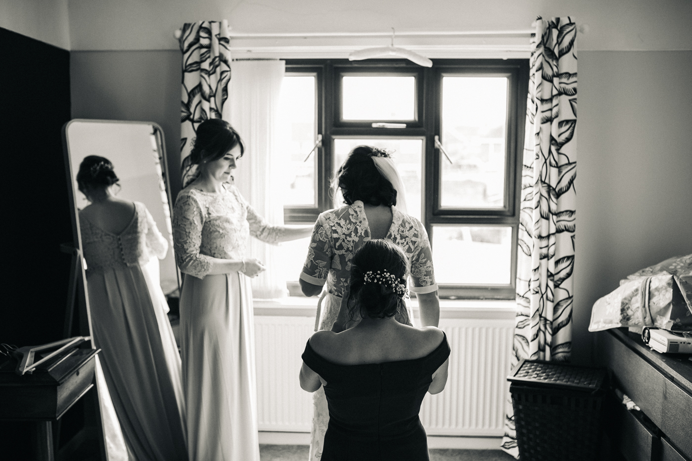 the bride is helped into her dress by her bridesmaids. ceremony at st georges hall liverpool, oh me oh my wedding reception, north west wedding photographer