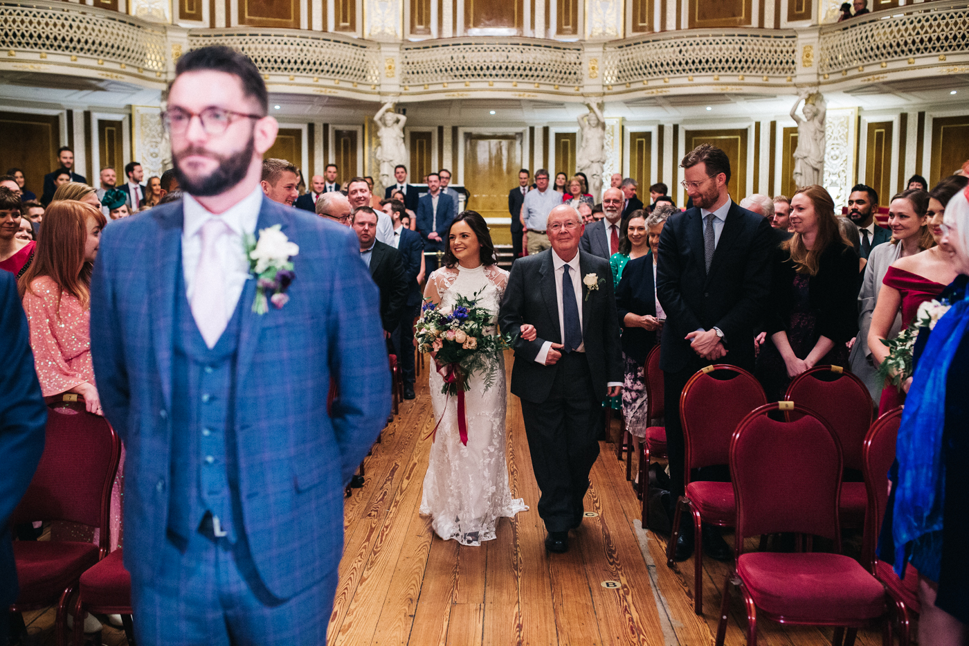the bride walks down the aisle with her dad, the groom doesn't turn around. ceremony at st georges hall liverpool, oh me oh my wedding reception, north west wedding photographer