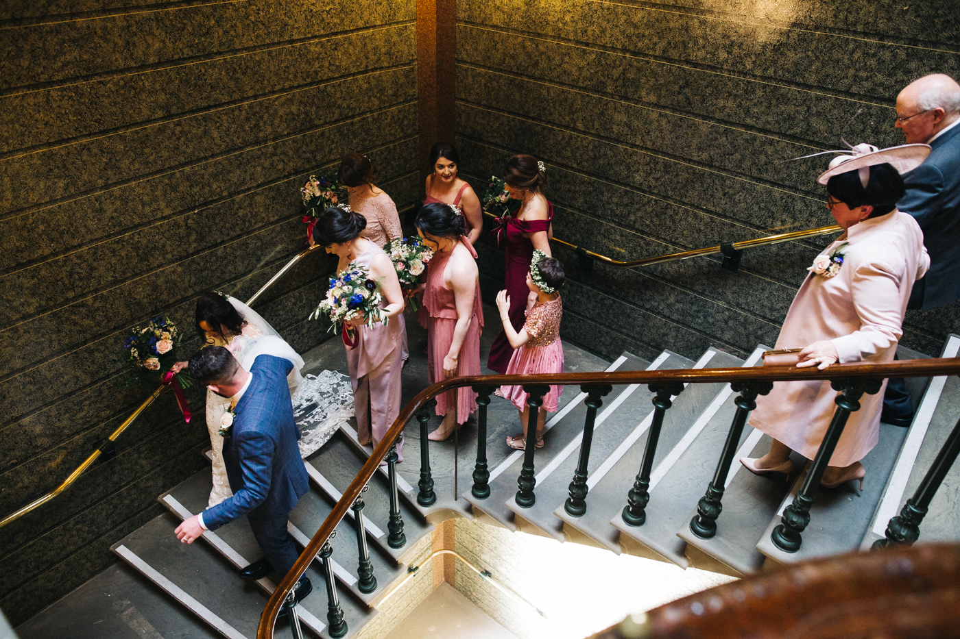 the bride, groom and bridal party walk down the stairs away from the ceremony. ceremony at st georges hall liverpool, oh me oh my wedding reception, north west wedding photographer