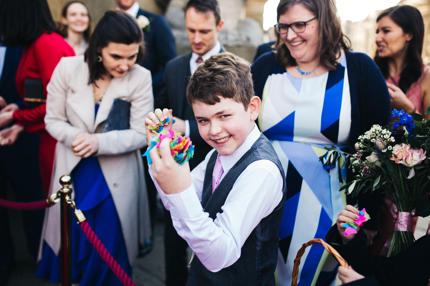 a boy stands armed with fistfuls of confetti. ceremony at st georges hall liverpool, oh me oh my wedding reception, north west wedding photographer