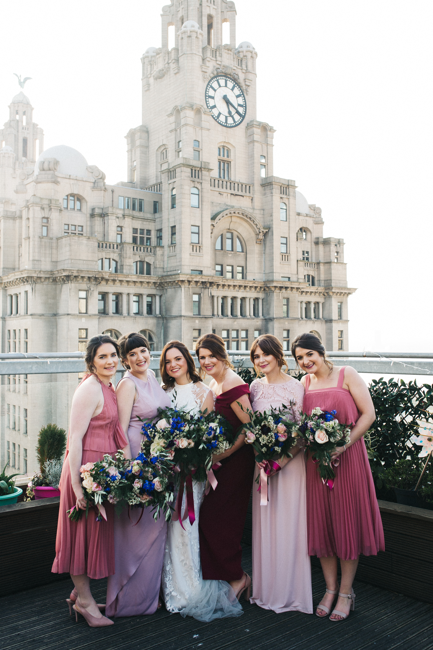 the bridesmaids stand smiling to camera in front of the liver building. ceremony at st georges hall liverpool, oh me oh my wedding reception, north west wedding photographer