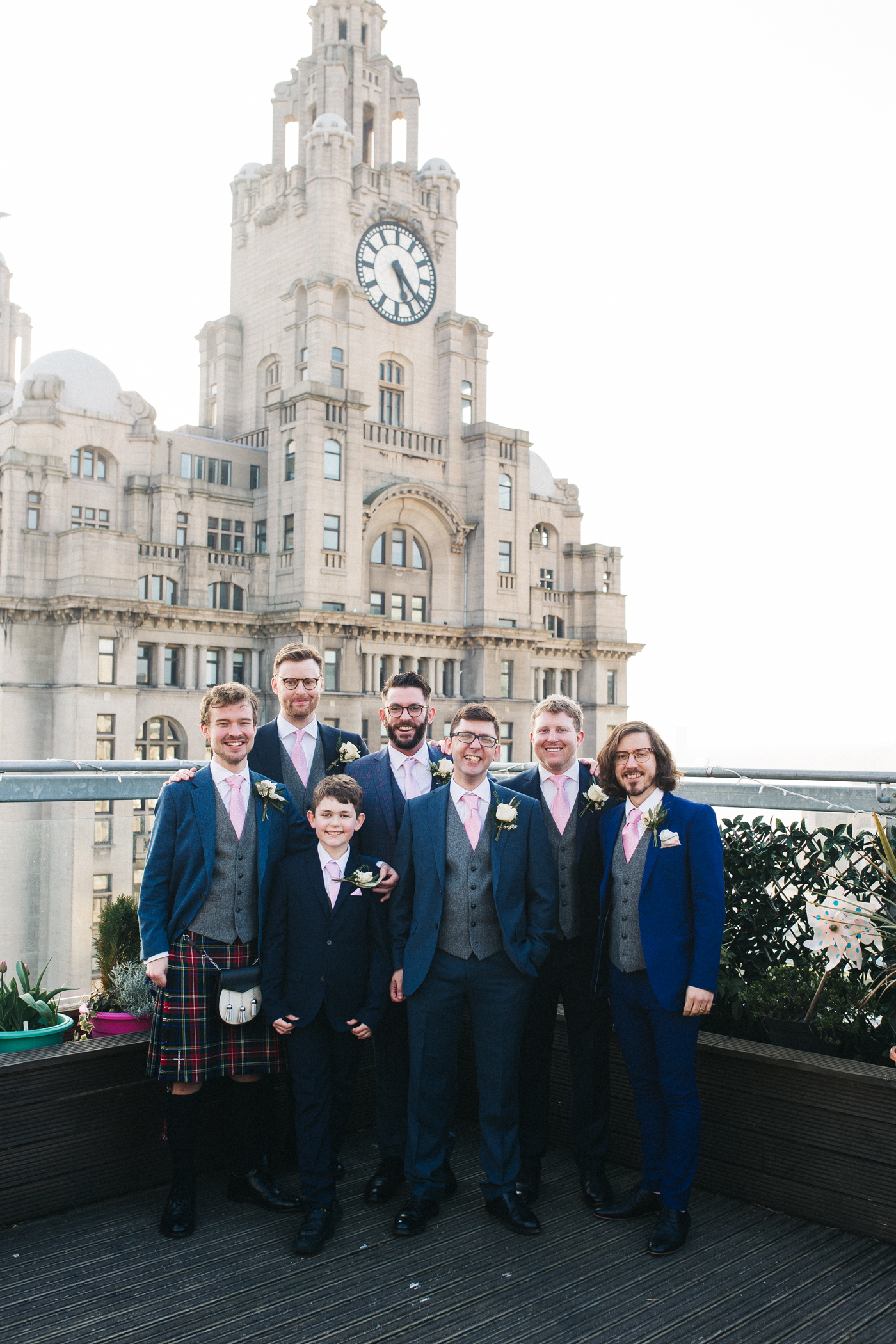 the groomsmen stand looking to camera in front of the liver building. ceremony at st georges hall liverpool, oh me oh my wedding reception, north west wedding photographer